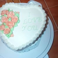 I Love You Double layer heart cake iced with buttercream and buttercream roses.
