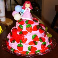 Strawberry Shortcake Three tier strawberry cake with strawberry icing, and lots of gummie strawberries.