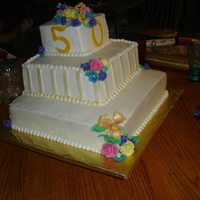 50Th Anniversary Anniversary cake with orchids, freesia, and roses made from gum paste. The stripes and the flowers were dusted with gold pearl dust.