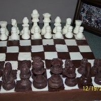 Chess Board Cake  Awesome Chocolate cake w/Chocolate Buttercream frosting..Chess pieces and Board all made with Chocolate..Made for my sons 29th Birthday......