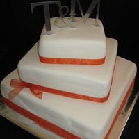 "Square Wedding Cake 16, 12, 8"" cakes covered in MMF and tied with an orange ribbon."