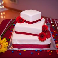 "Ivory And Red Wedding 14, 10, 6"" cakes covered in ivoery fondant and a red ribbon."