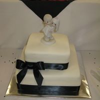 Precious Moments White MMF covered cake tied with a black ribbon and a Precious Moments topper.