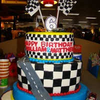 Matthew And Williams Race Car Cake White oval cakes with cream cheese filling and butter cream icing. Fondant decorations