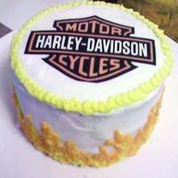 Harley-Davidson Anniversary Cake  White chocolate cake with a layer of white chocolate ganache and a layer of raspberry filling. Frosted in buttercream with an edible image...