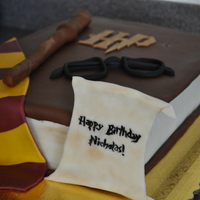 "Harry Potter Book Cake   Made for my son. Two 9x13"" cakes stacked and trimmed slightly. Covered with chocolate fondant and fondant decorations."