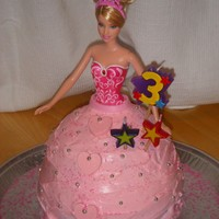 Princess Cake Chocolate cake covered in buttercream frosting with pink sugar and candy/fondant accents.