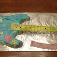 Peace & Love Guitar   Fondant covered and hand painted w/ gel colors. Gumpaste handle and buttercream strings
