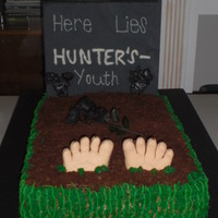 50Th B-Day Cake covered in buttercream, topped with crushed graham crakers and on the sides green buttercream. Feet made of gumpaste and headstone...