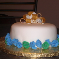 Anniversary/birthday This was on of my forswt cakes cakes. Cake covered in fondant with a gold fondant bow. Blue and green roses selected by the customer.