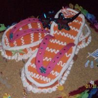"Beachy Fun! Flip Flop cake covered in BC. Gumpaste thong part with rhinestone details. Graham cracker crumb ""sand"" and scrapbooking stickers..."