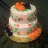 Two Tiered Wedding Cake Two tiered cake covered in Vanilla Buttercream with orange and dark purple roses