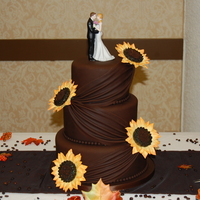 Sunflowers And Chocolate Wedding Cake Gumpaste sunflowers cover this 3 tier wedding cake covered in chocolate fondant with draping.