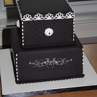 Black And White 2010 Cake covered in black fondant with white details. Bottom tier has a piped design.