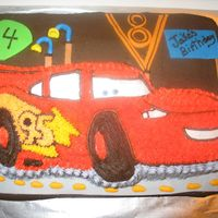 Lightening Mqueen   Lightening MCqueen on top of Chocolate Butter cream . With Fondant Pieces.