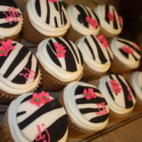 Zebra Cupcakes! Jumbo french vanilla cupcakes iced in buttercream with zebra print fondant circles and hot pink flowers. A few have the party guests and...