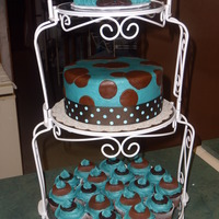 Baby Shower Tower Baby booties on top, round cake in buttercream and brown fondant dots with ribbon for border, chocolate cupcakes topped with reeeses and...