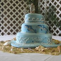 Dolphin Wedding Cake Paisley cake pans. White cake with passion fruit filling covered in fondant. Dolphins are fondant and all other decorations buttercream....