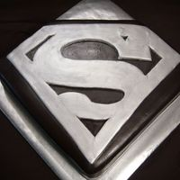 Superman 12x12 Yellow Cake cut to shape, bc fill, Chocolate Fondant colored black with a Silver Superman logo. used MMF dyed grey painted silver....