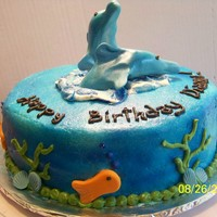 Dolphins In The Sea fondant hand-shaped dolphins, shells and fish. Butter cream covered cake airbrushed blue