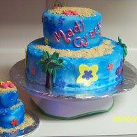 Luau buttercream with fondant accents, sand is graham crackers crushed and a smaller cake for the birthday girl