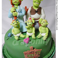 Shrek And Family Cake A cake inspired by Dreamworks' 'Shrek' movies, featuring gumpaste figurines of Shrek, Fiona and of the baby ogres triplets...