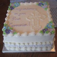 "Elizabeth's First Communion 8"" square white cake with almond butter cream. Royal icing flowers and lavender cornelli lace ""ribbon"" along the bottom."