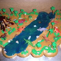 Dinosaur Cupcake Cake Vanilla and Chocolate cupcakes, BC icing, pretzel RI palm trees, Gel River and Volcano, Chocolate Rocks & Toy Dinosaurs.
