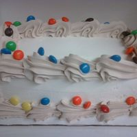 M&m Drops ice cream cake, paistry pride frosting, with fudge added for the border, topped with m&m's