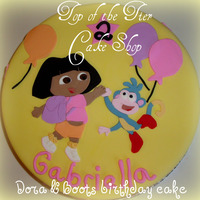 Dora & Boots Birthday Cake 11 inch vanilla cake w/ dulce de leche filling covered in fondant. I made a template of Dora & Boots and them out with fondant. TFL!