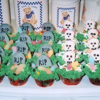 Graveyard Cupcakes  These are chocolate cupcakes filled with vanilla pudding and iced with buttercream. The tombstones and skulls are rolled out cookie dough...