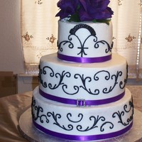 Purple Rose buttercream and black scrolls with purple flowers and ribbon.