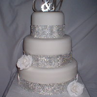 A Little Bling 3 tier (6, 9, 12) fondant covered with gumpaste rose and faux rhinestone banding.