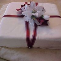 One Month Anniversary Cake White And Burgundy Lilies White Cake with Raspberry filling to mimic the wedding cake. Fondant in vanilla and a burgundy sheer ribbon adorn the cake. I had not...