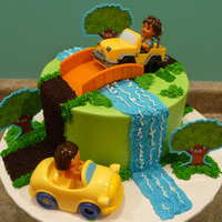 Dora And Diego Cake   frosted in buttercream... purchased plastic toy cars, bridge and trees... road is made out of crushed oreo cookies