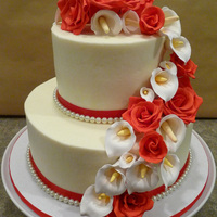 060610 Wedding   frosted in buttercream with red satin ribbon border and fake pearls, handmade gumpaste calla lilies and roses