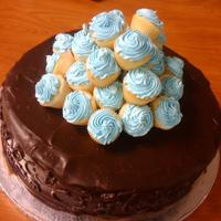 Chocolate Cake W/mini Cupcakes Chocolate ganache cake w/chocolate buttercream, topped w/light blue wasc mini cupcakes.