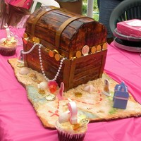 Princess And Pirates fondant covered pirate chest with sand, treasure map board and princess details, molded chocolate seashells, matching cupcakes