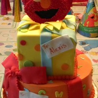 "Elmo Presents This was a cake for my twin nieces turning 2, wanted to keep the Elmo coloration ""girlie"" so I mixed in the aqua, yellow and..."