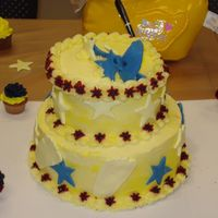Footprint And Stars Baby Shower 2 tier yellow double layer on bottom and yellow and chocolate on top tier. Covered in vanilla buttercream tinted in yellow. Red and blue...