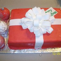 Christmas Present this is a white chocolate cake with rolled white chocolate fondant, there are 3 RKT ornaments, also covered in white chocolate fondant,...