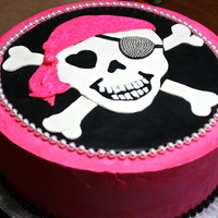 Skull And Cross Bones 3 tier yellow cake, filled with Nutella Buttercream. Pink Swiss Meringue Buttercream.Fondant decorations. Dragees on the eye patch for...