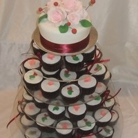 "Cupcake Wedding Tower  The 6"" cake as with the cupcakes are chocolate mudcake, decorated with sugar roses, pink cherry blossoms, sugar leaves and '..."