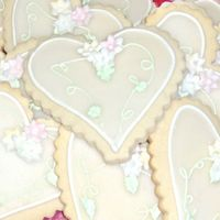 Wedding Favor Cookies - Hearts NFSC with royal, glaze, and MMF flowers. This pic is prior to them being bagged and tied with a silver bow and a tag with the couple info...