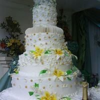 White And Yellow a 4 layer cake with gumpaste circles that look like host as separator between the top layer and next