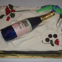 Wine And Roses Fondant cake, sugar wine bottle, gumpaste roses and chocolate candies.