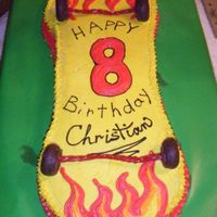 Flames Skateboard  Children's birthday cake for 8 yr old. Made w/ buttercream icing. Used a ciricle pan and a sheet cake. Used chocolate doughnuts &...
