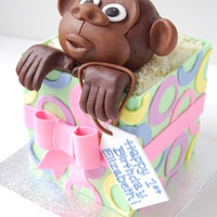 "Monkey In A Gift Box Birthday Cake By Charmpastry Chocolate cake with dark chocolate mousse 5"" cube covered with gumpaste panels to resemble gift box. Rice krispies treat head and..."