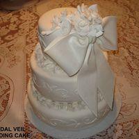 Bridal Veil Cake   My first wedding cake! Fondant, Gumpaste Flowers & Bow, Pearls, Scrolls. I am very pleased with it.