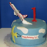Flying Airplane Cake Chocolate cake with chocolate ganache, covered in MFF. Fondant accents and gumpaste airplane.
